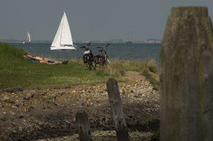 fietsers in gras tegen Oosterschelde met zeilboot